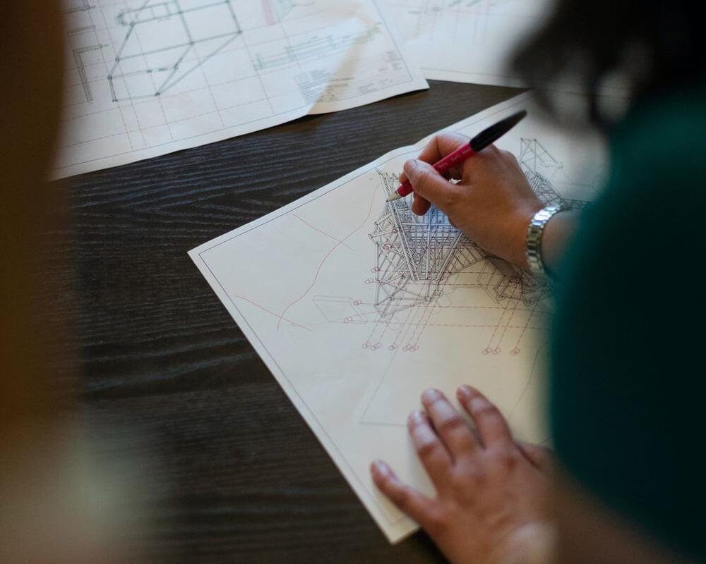 Person schreibt auf einen Bauplan